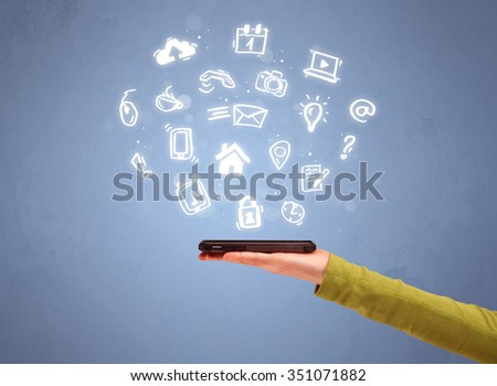 An elegant caucasian white hand holding mobile phone with drawn social media icons in front of an empty clear blue background concept - stock photo