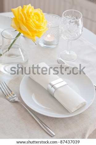 An elegant dining table setting with a white cloth and a yellow rose - stock photo