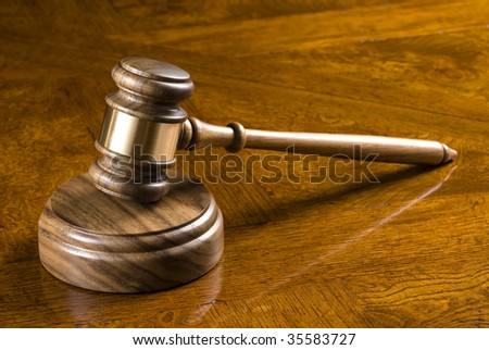 An elegant gavel and block on an deep, richly colored wooden desk. - stock photo