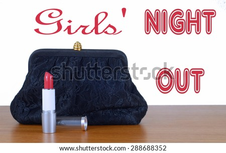 An elegant, lacy black clutch woman's evening bag laying on a wooden table, isolated on white. Red lipstick is opened. Concept of feminine glamour and party or celebration. Isolated on white with text - stock photo