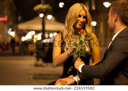 An elegant man giving his date a red rose - stock photo