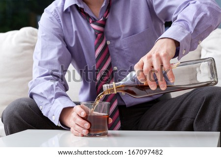 An elegant man suffering from alcoholism drinking whisky - stock photo