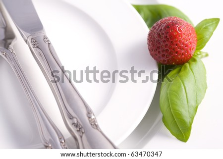An elegant restaurant table setting with a strawberry and some basil as accent. - stock photo