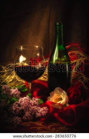 An elegant scene with a glass of red wine next to wine bottle surrounded by lilac, roses and luxurious cloth in soft, warm lighting. - stock photo