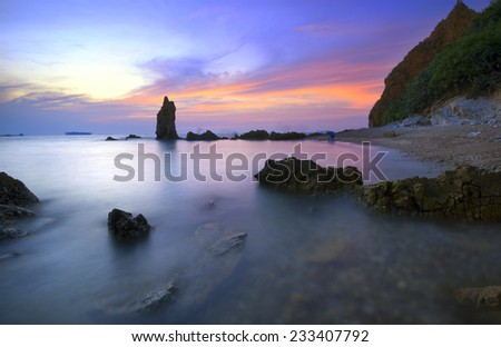 An elegant stone bars stand in bright candy colors beautiful sunset beach area of Thailand. - stock photo