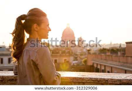 An elegant woman tourist is standing looking out at the sunset from a ledge in the city of Rome. - stock photo