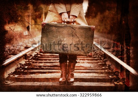 An elegant woman with a suitcase traveling by rail. Photos in the grunge style. - stock photo