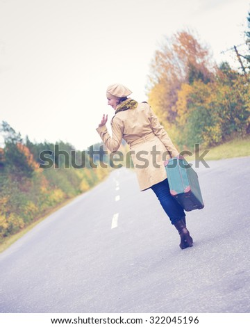 An elegant woman with a suitcase traveling the highway autumn day.