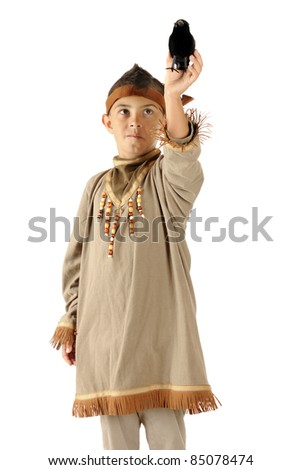An elementary boy dressed as a native American Indian holding a big black bird up to take off from his hand.  Isolated on white. - stock photo
