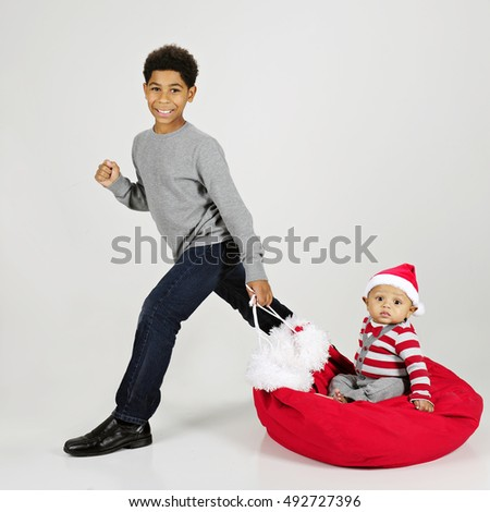 An elementary boy happily taking his baby brother on a Santa bag ride.  On a gray background.