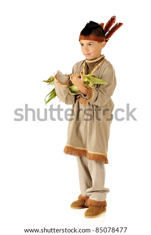 An elementary boys dressed as a native American, carrying an armload of corn for the Thanksgiving feast.  Isolated on white. - stock photo