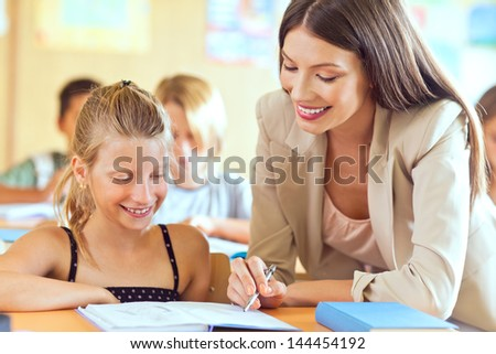 An elemetary school teacher helping one of her students. - stock photo
