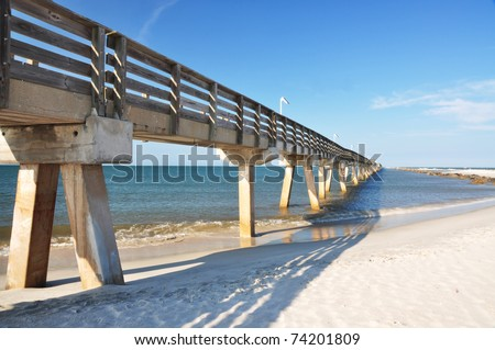an elevated bridge projecting into the sea (Fort Clinch State Park, FL) - stock photo