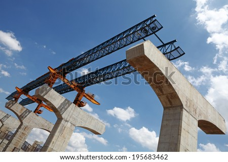 An elevated highway gantry crane extender mechanical guide at a construction site against a blue cloudy sky.