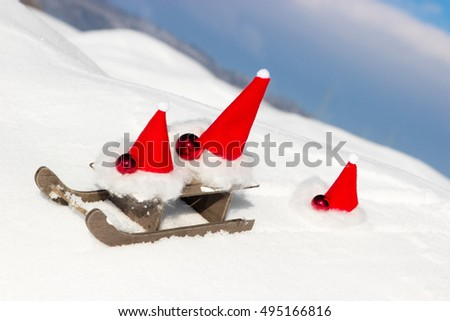 An elf is behind a sled with two imps in the snow