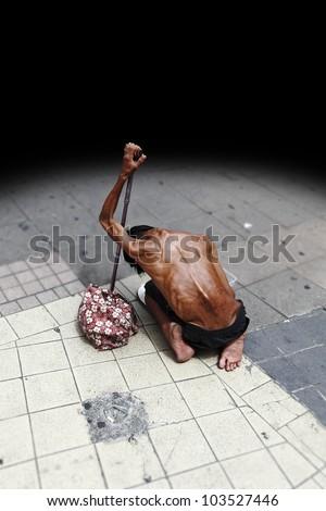 An emaciated heavily sun tan homeless man begging on a street pavement. - stock photo