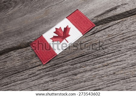 An embroidered Canadian flag patch sits on a grungy wooden plank. - stock photo