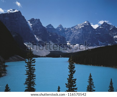 An emerald colored lake in the valley between snowy mountains - stock photo