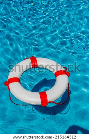 an emergency tire floating in a swimming pool. symbol photo for rescue and crisis management in the financial crisis and banking crisis. - stock photo