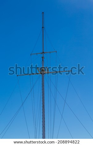 An empgy ship's mast against a clear blue sky - stock photo
