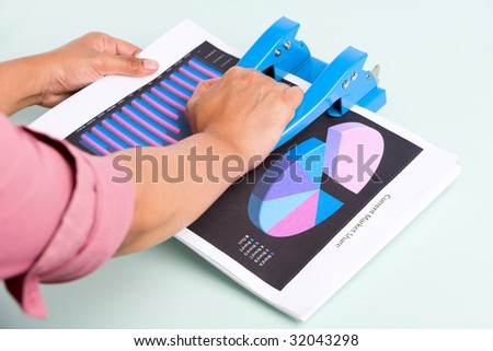 An employee is pressing the hole puncher to make hole on documents. - stock photo