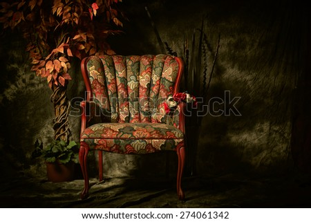 An empty, antique patterned chair shot in a chiaroscuro lighting style sitting next to artificial plant. - stock photo