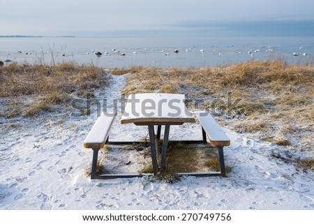 An empty bench on the beach in winter - stock photo