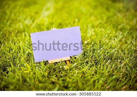 an empty blackboard with place for your text  on green lawn  - stock photo