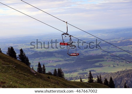 an empty chairlift spanning over a summer landscape