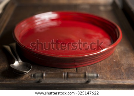 An empty, crimson red, circular shallow serving dish with a pair of spoons in a wooden tray.