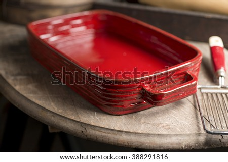 An empty crimson red rounded rectangular baking dish beside a vintage egg slicer placed on edge of a wooden countertop.