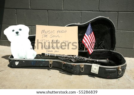 an empty guitar case with a sign and a cardboard cut out of a bichon frise dog asking for tips to play music - stock photo