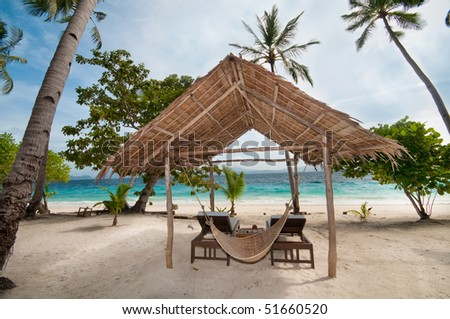 An empty hut and a hammock on a tropical beach
