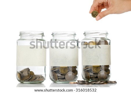 An empty label of glass jars with coins like diagram with woman right hand want to put coin on it isolated on white background - savings, financial, loan, retirement, and home concept - stock photo