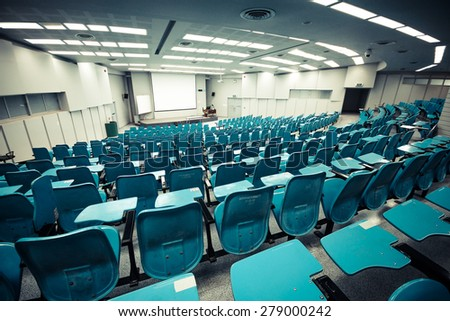 An empty large lecture room / University classroom with blue chairs - stock photo