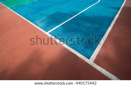 An empty, outdoor, colorful basketball court in Thailand with the sky and clouds in the background - stock photo