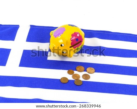An empty piggy bank on the Greek flag with small euro coins - stock photo