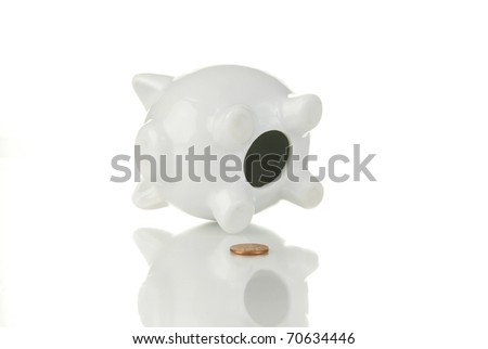 An empty piggy bank with only a penny indicating poverty or being broke - stock photo