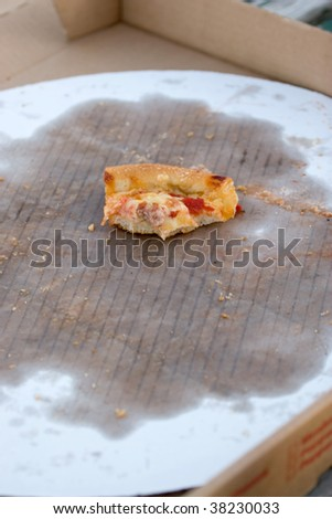 An empty pizza box with one scrap of a piece remaining in the greased up cardboard container. - stock photo
