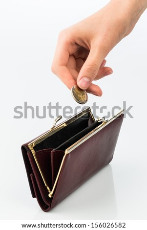 an empty purse and a hand holding a coin against white background - stock photo