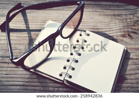 An empty retro spiral notebook with old paper and reading glasses