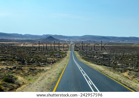 An empty road in the Namibian desert - stock photo