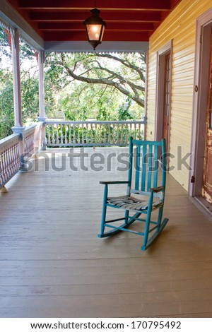 An empty rocking chair on an old porch - stock photo