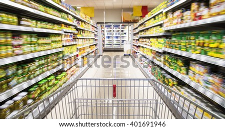 An empty shopping cart between rows of shelves in the supermarket.