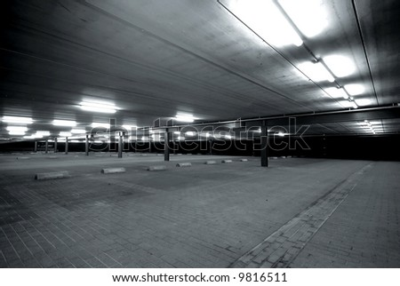 an empty spacious parking lot in black and white - stock photo