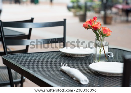 An empty table for an outdoor restaurant. On the table are two white plates, silverware wrapped in a white napkin, and flowers in a clear glass vase.  - stock photo