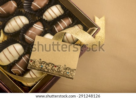 An empty tag with golden ribbon on a box filled with fine quality date-chocolates. - stock photo