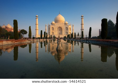 An empty Taj Mahal glows beautifully at sunrise as it's reflected in a calm water fountain. - stock photo