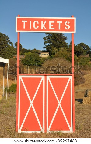An empty ticket booth in a field with hay stacks.