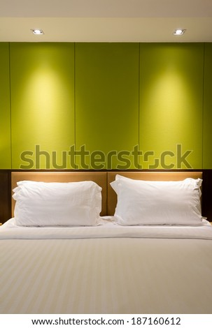 An empty wall over a bed with spotlight for advertising or picture frame - stock photo
